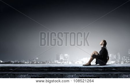 Bored young businesswoman sitting alone on roof