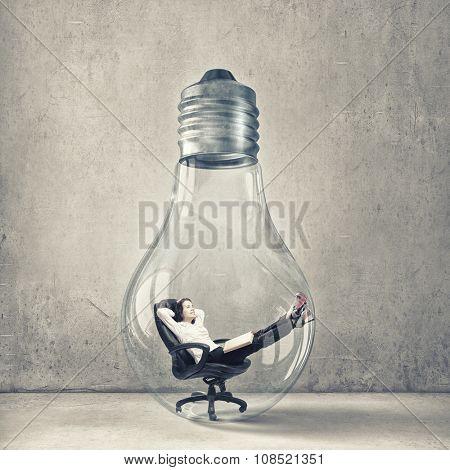 Relaxed businesswoman sitting inside of glass light bulb