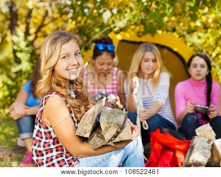 Happy beautiful girl holding kindling wood in camp