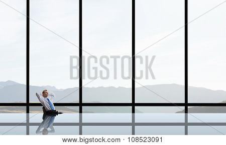 Relaxing businessman with crossed hands behind his head in office