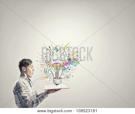 Young emotional guy with opened book in hands
