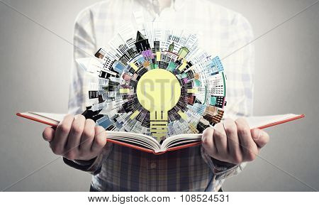 Young man holding opened book and idea bulb on pages