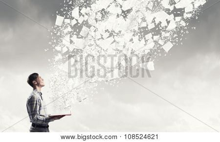 Young man with opened book in hands and pages flying in air