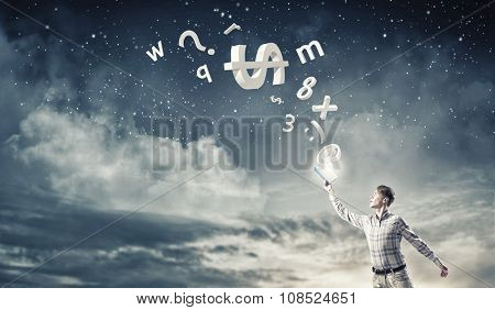 Young handsome man reaching hand with book and characters flying out