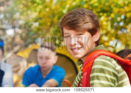 Close-up of boy with rucksack near yellow tent