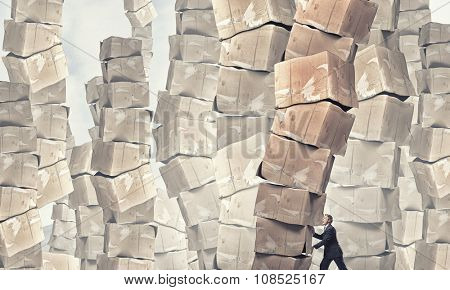 Young businessman making effort to move stack of carton boxes