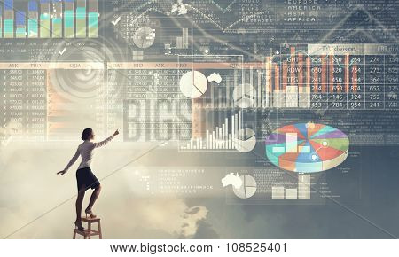 Back view of businesswoman standing on chair and reaching infographs on wall
