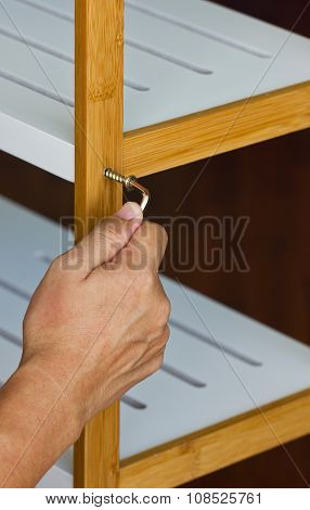 Asian Man's Hand Screw Up Wooden Shelf With Hex Wrench.