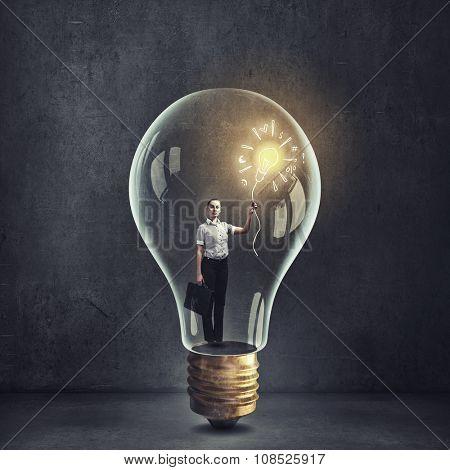 Businesswoman inside glass light bulb on dark background