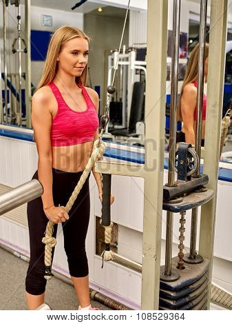 Girl workout on bicep curl machine with rope in sport gym.