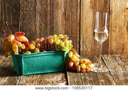 Fresh grapes and glass of grappa on old wooden table