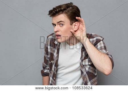 Curious young handsome male in plaid shirt trying to listen rumors