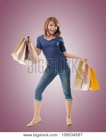 Smiling happy Asian woman shopping and holding bags, full length portrait isolated