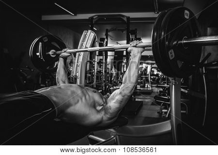 Brutal athletic man pumping up muscles on bench press in monochrome