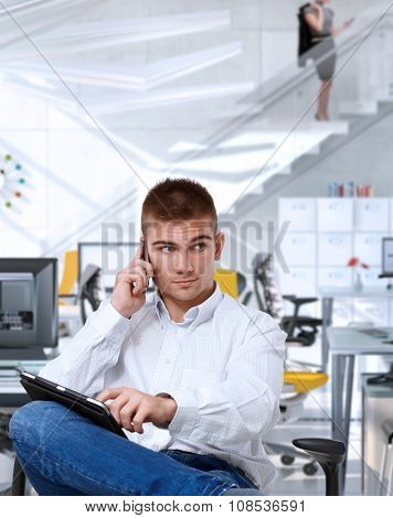 Young casual caucasian business office worker with mobile phone, sitting, with tablet in lap. Copyspace.