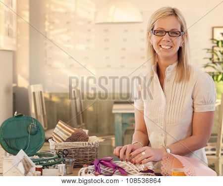 Happy casual caucasian blonde mid adult businesswoman making valentine day wreath at home. Smiling, wearing glasses, standing at table, do it yourself, gift, present. Looking at camera.