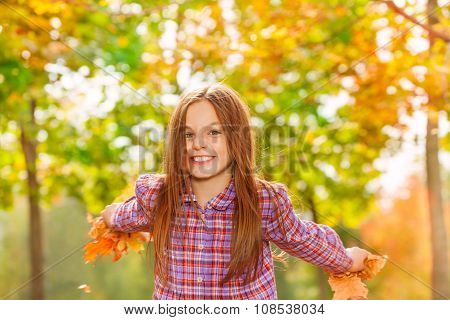 Happy little girl throw maple leaves in the air