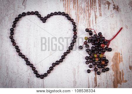 Heart Of Fresh Elderberry On Old Wooden Background, Symbol Of Love