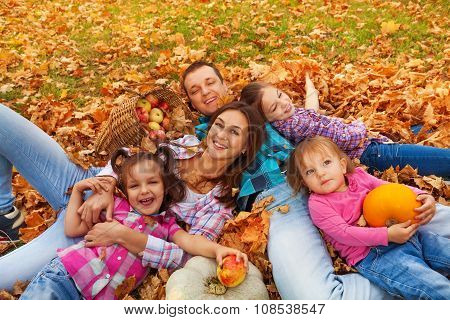 Family with three girls lay in the maple leaves