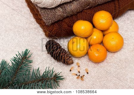 Christmas and New Year Mandarins in the snow next to the multi-colored sweaters, pine cones and Chri
