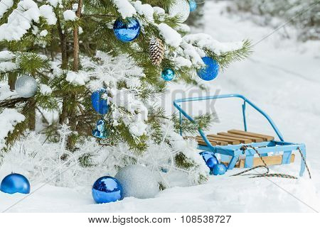 Christmas snowy pine tree decorated with glitter baubles and blue sledge on snow covering