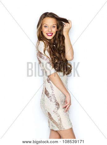 people, style, holidays, hairstyle and fashion concept - happy young woman or teen girl in fancy dress with sequins touching long wavy hair