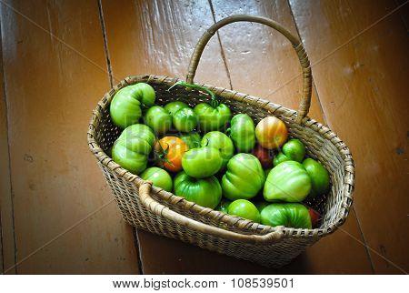 Unripe tomatoes in a wicker basket