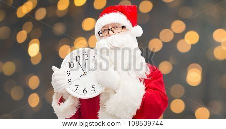 christmas, holidays, time and people concept - man in costume of santa claus with clock showing twelve pointing finger over golden lights background