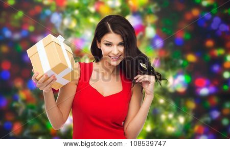 people, holidays, christmas, birthday and celebration concept - beautiful sexy woman in red dress with gift box over party lights background