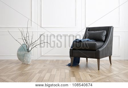 Comfortable black leather armchair in a minimalist living room interior with white panelled walls, hardwood floor and a vase with twigs. 3d Rendering.