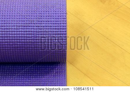 the old Yoga mat on wood background.