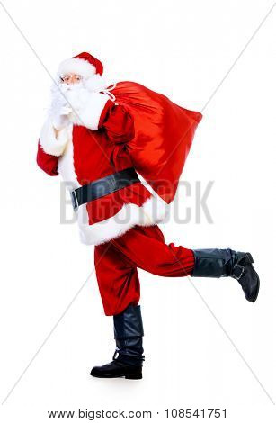 Santa Claus in a hurry with gifts for the holiday. Christmas celebration. Isolated over white.