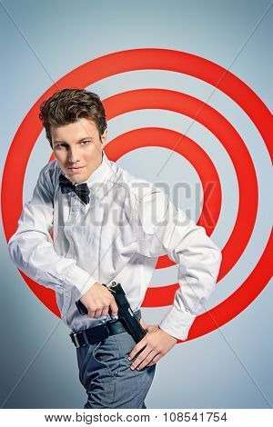 Elegant handsome man secret agent with a gun posing by a red shooting target. Spy man.