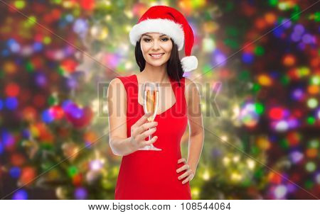 people, holidays, christmas and celebration concept - beautiful sexy woman in santa hat and red dress with champagne glass over party lights background