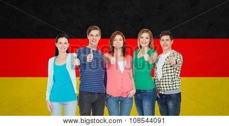 education, nationality, gesture and people concept - group of smiling friends or students standing and showing thumbs up over german flag background
