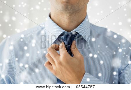 people, business, fashion and clothing concept - close up of man in shirt dressing up and adjusting tie on neck at home over snow effect