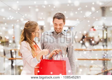 sale, consumerism and people concept - happy young couple showing content of shopping bags in mall with snow effect