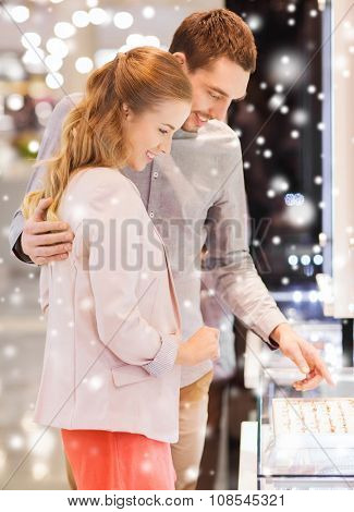 sale, consumerism, shopping and people concept - happy couple choosing engagement ring at jewelry store in mall with snow effect