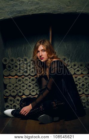 Young Woman Sitting On The Floor In Wine Vault