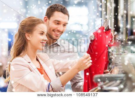 sale, consumerism and people concept - happy young couple with shopping bags choosing dress in mall with snow effect