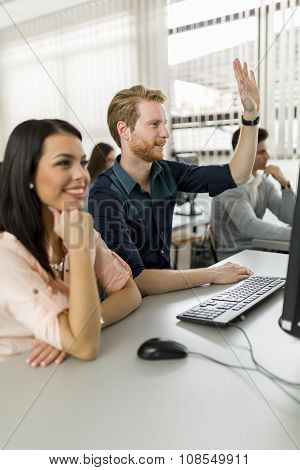 Beautiful Young Woman And A Man Raising Hands In Classroom