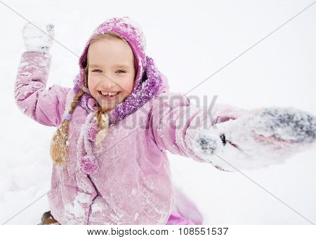 Child in winter. Happy girl on snow. Playing snowballs