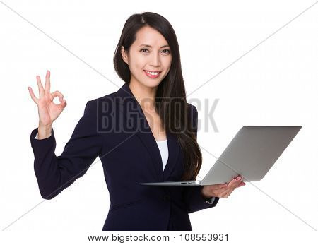 Young Businesswoman hold with notebook computer and ok sign gesture