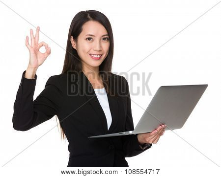 Young Businesswoman use of the laptop computer with ok sign gesture
