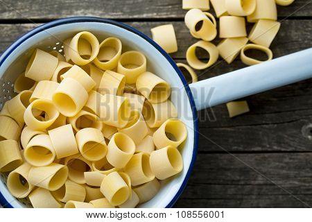 uncooked pasta calamarata in colander