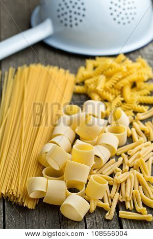 various uncooked pasta on old wooden table