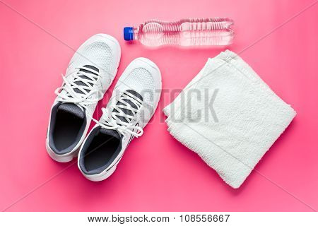 sport concept. bottle, shoes and towel on pink background