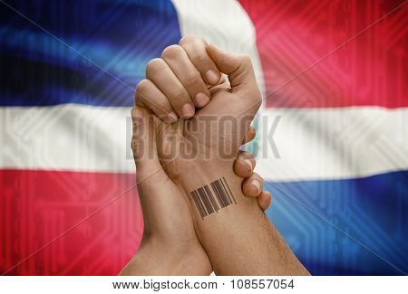 Barcode Id Number On Wrist Of Dark Skinned Person And National Flag On Background - Dominican Republ