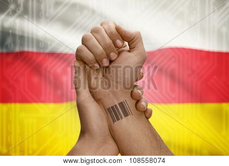 Barcode Id Number On Wrist Of Dark Skinned Person And National Flag On Background - South Ossetia