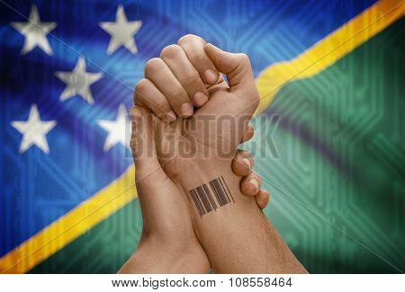 Barcode Id Number On Wrist Of Dark Skinned Person And National Flag On Background - Solomon Islands